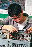 Teenager male intern working computer parts salvaging repairing vertical
