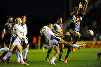Jonathan Joseph of Bath Rugby clears as Charlie Matthews of Harlequins attempts to block the kick