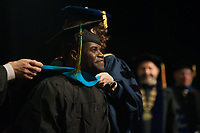 Melchisedek Jean, PADM MPA, is hooded during the UAA Spring 2018 Graduate Degree Hooding Ceremony.