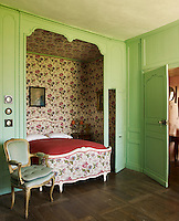 The alcove of this green panelled bedroom is covered in a floral fabric to match the bed