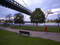 """USA. New York City. Queens. Astoria park. The Robert F. Kennedy (RFK) Bridge, formerly known as the Triborough Bridge (sometimes spelled Triboro Bridge), is a complex of three separate bridges. Spanning the Harlem River, the Bronx Kill, and the Hell Gate (part of the East River), the bridges connect the boroughs of Manhattan, Queens, and The Bronx via Randall's Island and Wards Island, which are joined by landfill. Often still referred to as simply the """"Triboro"""" the spans were officially named after Robert F. Kennedy in 2008. Night view on the Hudson river.  A man does his jogging. 21.10.2011 © 2011 Didier Ruef"""