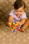 7 month old baby girl sitting waving toy