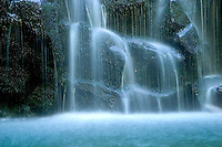 Water forms a mist at the base of a waterfall