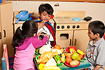 Education Preschool group of three children playing in pretend play area interaction girl offering play food to boy