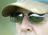 Ed Wille keeps an eye on his alpacas as they graze in a field Sunday, July 2, 2006, in Valley City, Ohio. Ed, who raises 23 alpacas with his wife Barb, say they have earned $200,000 since starting up in 1994 by selling alpacas, winning stud fees and housing 12 of the furry creatures for $3 a day.<br />