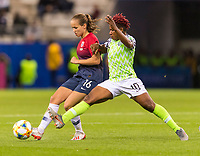 REIMS, FRANCE - JUNE 08: Guro Reiten #16 passes the ball away from Rita Chikwelu #10 during a game between Norway and Nigeria at Stade Auguste-Delaune on June 8, 2019 in Reims, France.