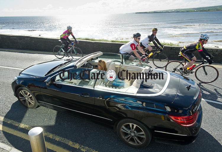 Everyone to their own as the cyclists pass an open top car on the way into Lahinch during the second day of the Clare 250 Cycle. Photograph by John Kelly.