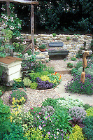 Beautiful herb garden, edible flowers Nasturtiums Tropaoleum Alaska, stone wall, purple basil, thymes, mixture of different herbs in charming setting, stone pebble pathway edged in bricks, Warre beehive, viola, lavenders, ornament, sign quote, climbing roses