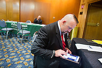 D. R. Lacy, an Army Veteran from Elmira, New York, fills out his contact information for a driver profile with Uber after speaking with Uber representatives who asked not to be named at the Recovering Warrior Employment Conference at the Back Bay Event Center in Boston, Massachusetts, USA. Lacy said that if Uber existed when he was younger, it would have been perfect for him, but he was at the conference looking at employment opportunities that would use his technical experience more than Uber would.<br /> <br /> The employment conference was organized by Hiring Our Heroes and Wounded Warrior Project. Hiring Our Heroes is an initiative of the US Chamber of Commerce Foundation. Approximately 40 veterans registered for the event, during which they had interviews with a number of different regional and national employers, including GE, Bank of America, Uber, and others.
