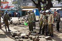 Kenya. Rift Valley province. Nakuru. 25.01.2008. A group of Kikuyu policemen with military outfitts looks at the body of a dead black man from the Kalenjin tribe. One policeman checks the identity card. The man, lying on the ground, was lynched by a group of men, stoned to death and his body set on fire. Inter-ethnic strife. Ethnic cleansing and purification. Capital offense. The Kikuyus are Kenya's most populous ethnic group. Kalenjin is another ethnic group of Nilotic origin living in the Great Rift Valley in western Kenya. © 2008 Didier Ruef