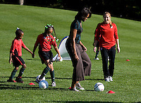 Michelle Obama rounds a cone during a Lets Move! soccer clinic held on the South Lawn of the White House.  Let's Move! was started by Mrs. Obama as a way to promote a healthier lifestyle in children across the country.