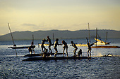 Bahia, Brazil. Children playing on canoes in the sea.