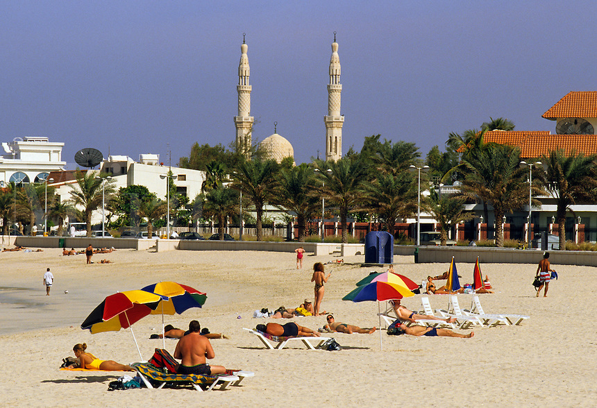 Dubai, UAE. Jumeira/Jumeirah beach.  Sun worshipers on the beach overlooked by the minarets of a mosque..