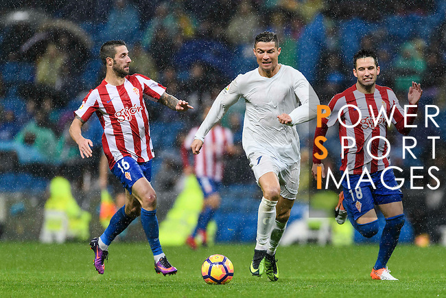 """Cristiano Ronaldo (c) of Real Madrid battles for the ball with Manuel Castellano """"Lillo"""" (l) and Ismael Lopez Blanco """"Isma"""" of Real Sporting de Gijon during the La Liga match between Real Madrid and Real Sporting de Gijon at the Santiago Bernabeu Stadium on 26 November 2016 in Madrid, Spain. Photo by Diego Gonzalez Souto / Power Sport Images"""