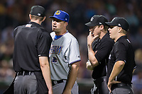 Durham Bulls manager Jared Sandberg (22) argues a call with home plate umpire Eric Gillam as umpires Alex Tosi (center) and Brian Peterson look on during the game against the Charlotte Knights at BB&T BallPark on May 15, 2017 in Charlotte, North Carolina. The Knights defeated the Bulls 6-4.  (Brian Westerholt/Four Seam Images)
