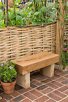 Wooden garden bench against willow woven fence in garden