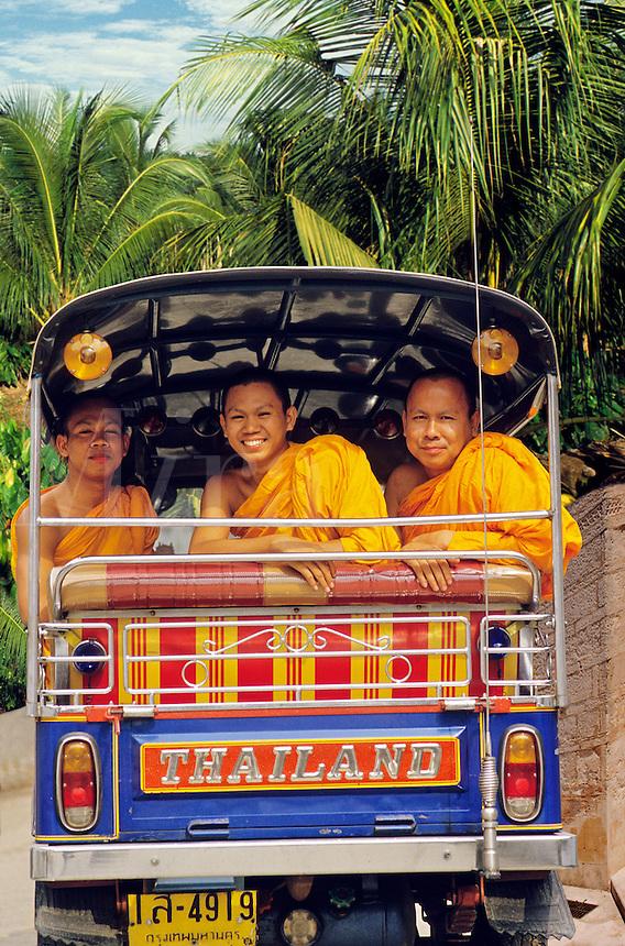 Three young Buddhist monks share a tuktuk. Bangkok. Thailand