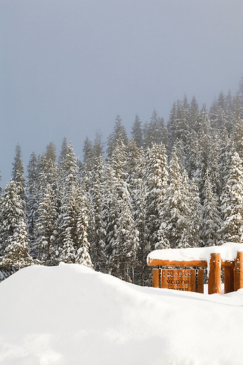 A sign at the Lolo Pass Visitor Center in winter covered in snow