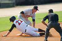 Jake Oester #22 of the Kannapolis Intimidators slides head first into third base with a triple ahead of the tag by Stephen King #21 of the Hagerstown Suns as umpire Aaron Roberts looks on at Fieldcrest Cannon Stadium August 8, 2010, in Kannapolis, North Carolina.  Photo by Brian Westerholt / Four Seam Images