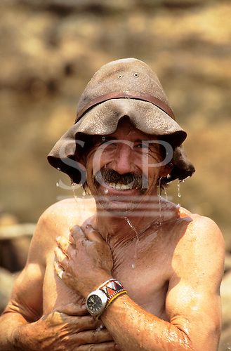 Lukulu, Zambia. Smiling man in wet battered bush hat with water dripping onto his face and body; David Maskell.