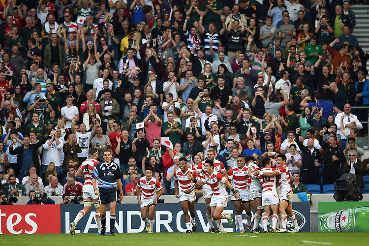 The Japan team celebrate a second half try by Ayumu Goromaru. Rugby World Cup Pool B match between South Africa and Japan on September 19, 2015 at the Brighton Community Stadium in Brighton, England. Photo by: Patrick Khachfe / Stewart Communications