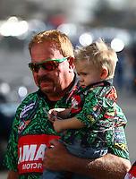 Feb 8, 2015; Pomona, CA, USA; NHRA top fuel driver Terry McMillen holds son Cam McMillen during the Winternationals at Auto Club Raceway at Pomona. Mandatory Credit: Mark J. Rebilas-