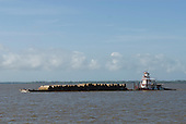 Pará State, Brazil. The Amazon River. Barge laden with logs from the rainforest.