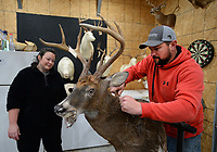 """Justin Clark (right), owner of Red Arrow Taxidermy, and associate Ashley Metheny Smith work together Wednesday, Jan. 6, 2021, to finish a deer mount for a customer in Clark's workshop in Hogeye. Clark, a retired Fayetteville firefighter, has a thriving business that he began in his garage several years ago. """"It's never not deer season for me,"""" Clark said. Visit nwaonline.com/210107Daily/ for today's photo gallery. <br /> (NWA Democrat-Gazette/Andy Shupe)"""