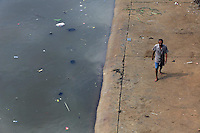 A man walks past a heavily polluted waterway in central Jakarta.<br /> <br /> To license this image, please contact the National Geographic Creative Collection:<br /> <br /> Image ID:1588067<br />  <br /> Email: natgeocreative@ngs.org<br /> <br /> Telephone: 202 857 7537 / Toll Free 800 434 2244<br /> <br /> National Geographic Creative<br /> 1145 17th St NW, Washington DC 20036