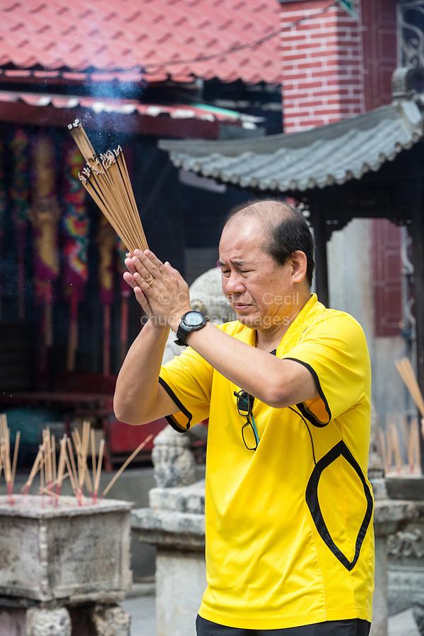 George Town, Penang, Malaysia.  Worshiper Praying with Joss Sticks (Incense) outside Goddess of Mercy Temple, Kuan Yin Teng, Kong Hock Keong.