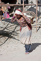 Kathmandu, Nepal.  Nepali Woman Carrying Basket of Stones for Mixing with Cement.