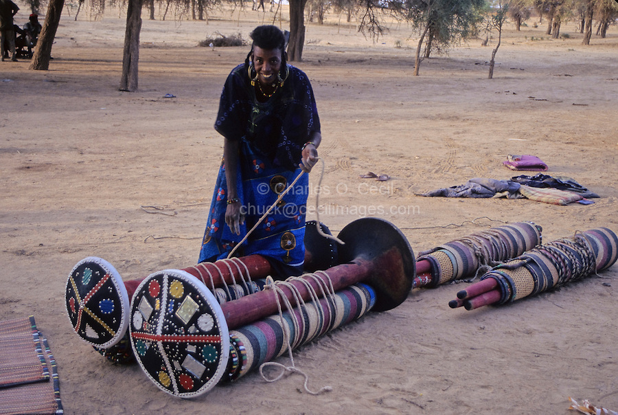 Akadaney, Central Niger, West Africa.  Fulani Nomads.  Woman Tying up Bed Components Prior to Loading on Donkey.