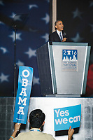 """A man holds signs reading """"Obama"""" and """"Yes We Can"""" as President Barack Obama speaks at the Democratic National Convention at the Wells Fargo Center in Philadelphia, Pennsylvania, on Wed., July 27, 2016."""
