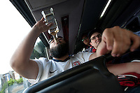 A USA fan enjoys a drink of tequila while on a bus of traveling supporters.  Mexican police officers in riot gear formed a perimeter around the bus of USA fans before USA vs. Mexico World Cup Qualifier at Azteca stadium in Mexico City, Mexico on March 26, 2013.