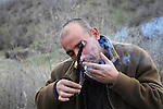 BASHMAKH, IRAQ:  Swara who is the caretaker for the smugglers den lights his cigarette with a burning branch...Iranian Kurdish smugglers traffic petrol from Iran into Iraq and alcohol from Iraq into Iran.  On foot, a smuggler can look to make around $10 per trip whereas with a horse a smuggler can make $100.  The routes are very dangerous with the risk of stepping on land mines or  being shot by the Iranian military..Photo by Kamaran Najm/Metrography