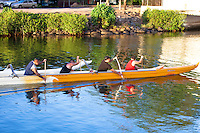 Local men paddling a canoe on Anahulu Stream in Haleiwa, O'ahu.