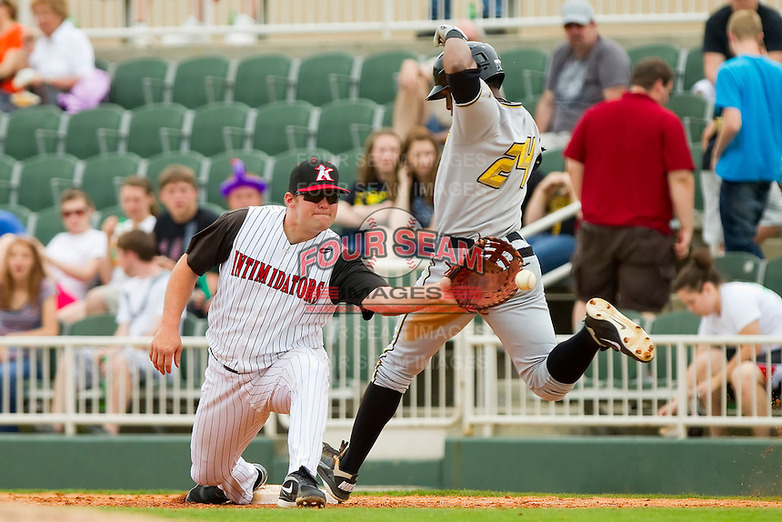 First baseman Dan Black #40 of the Kannapolis Intimidators stretches for the throw as Mel Rojas Jr. #24 of the West Virginia Power beats out a bunt at Fieldcrest Cannon Stadium on April 20, 2011 in Kannapolis, North Carolina.   Photo by Brian Westerholt / Four Seam Images
