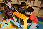 Education preschool 4 year olds group of three boys playing with doll house and toy dinosaurs