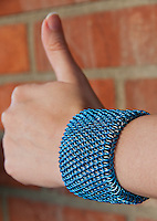 """A blue and silver dragonscale weave maille bracelet on a hand showing the thumbs-up sign.  It's made from saw cut 18 gauge 1/4"""" ID blue anodized aluminum rings and saw cut 19 gauge 5/32"""" ID bright aluminum rings.  The clasp is a gunmental plated slide clasp.   Handmade by Michelle."""