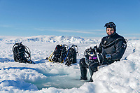 ice diving - underwater photographer; Tobias Friedrich, sitting on the edge of the ice, ready to dive under the ice with the hole right in front of him, holding his underwater camera with dive gear in the background, Semalik Fjord, near Tasiilaq, Greenland, Atlantic Ocean, photo by Thomas Fiebig