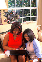 African American mother with daughter with laptop computer at home.