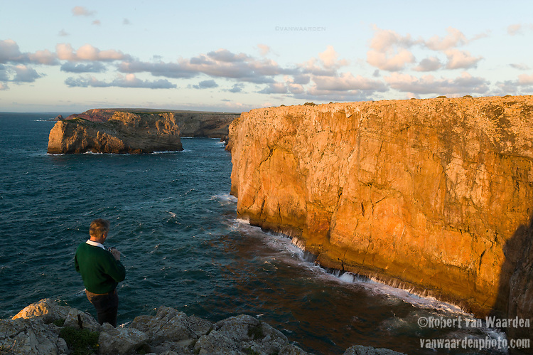 A man photographs the cliffs of Sagres and the waves of the Atlantic in the Algarve region of Portugal.