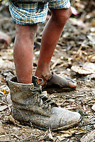 8 year old Alamin wears a policeman's shoe, which he has found among the piles of waste on Kajla rubbish dump.  It is one of three landfill sites in this city of twelve million people.  Around 5,000 tonnes of garbage are dumped here each day and over a thousand people work among the rubbish, sorting through the waste and collecting items to sell to retailers for recycling.