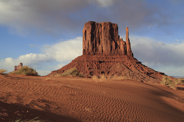 The Mitten rock formation and sand dunes in Monument Valley, Arizona, USA. . John offers private photo tours in Monument Valley and throughout Arizona, Utah and Colorado. Year-round.