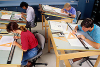 Students boys and girls in High school 11th grade drafting class with draft tables working in schoo