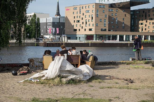 """Die """"Cuvry-Brache"""" in Berlin-Kreuzberg.<br /> Ein Investor will auf dem seit Jahrzehnten leerstehenden Gelaende direkt an der Spree einen lukrativen Geschaeftskomplex mit Wohnanteil bauen. Auf der """"Cuvry-Brache"""" haben sich in den vergangenen Jahren Obdachlose, und Aussteiger mit Zelten und selbstgebauten Huetten angesiedelt. Am Spreeufer geniessen Jugendliche im Sommer die Abende.<br /> Allerdings gibt es auch immer wieder Probleme und Auseinandersetzungen unter den Bewohnern der """"Cuvry-Brache"""", die nur durch die Polizei geschlichtet werden koennen.<br /> 16.6.2014, Berlin<br /> Copyright: Christian-Ditsch.de<br /> [Inhaltsveraendernde Manipulation des Fotos nur nach ausdruecklicher Genehmigung des Fotografen. Vereinbarungen ueber Abtretung von Persoenlichkeitsrechten/Model Release der abgebildeten Person/Personen liegen nicht vor. NO MODEL RELEASE! Don't publish without copyright Christian-Ditsch.de, Veroeffentlichung nur mit Fotografennennung, sowie gegen Honorar, MwSt. und Beleg. Konto:, I N G - D i B a, IBAN DE58500105175400192269, BIC INGDDEFFXXX, Kontakt: post@christian-ditsch.de]"""