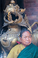 Nepal, Kathmandu.  Hindu Woman by Lion Sculpture, Akash Bhairab Temple.  The temple survived the earthquake of April 2015.