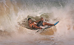 A boarder gets comfortable on his board as he slides through a wave at Sandy Beach in Hawaii.