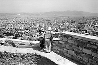 Greece. Attica Region. Athens. A couple of tourists takes pictures and films videos while standing on the Acropolis which is an ancient citadel located on a high rocky outcrop above the city of Athens and containing the remains of several ancient buildings of great architectural and historic significance. Clear day and open view on the city. Athens is the capital and largest city of Greece. © 1992 Didier Ruef