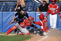 State College Spikes catcher Luis Cruz (4) loses the ball as Carlos Duran (25) scores a run with umpire Matt Carlyon in position to make the call during a game against the Batavia Muckdogs on June 22, 2014 at Dwyer Stadium in Batavia, New York.  State College defeated Batavia 10-3.  (Mike Janes/Four Seam Images)